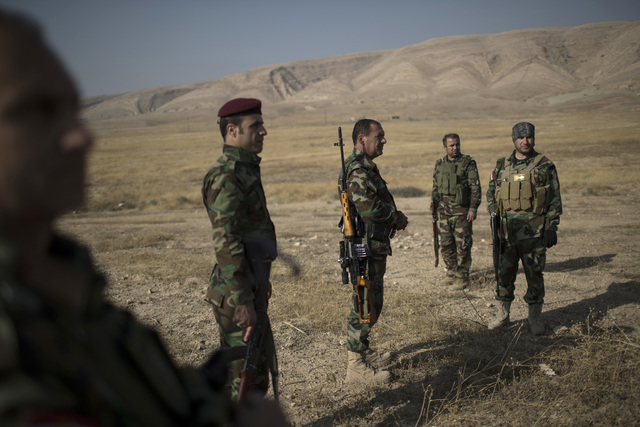 FILE - In this Tuesday, Nov. 8, 2016, file photo, Kurdish Peshmerga fighters gather near a frontline during fighting with Islamic State militants in Bashiqa, east of Mosul, Iraq. Human Rights Watc ...