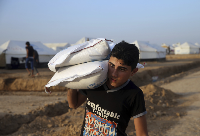 A displaced Iraqi man, who fled from Mosul,carries bags of flour at a camp for internally displaced people in Hassan Sham, east of Mosul, Iraq. The urban landscape inside Mosul proper makes defens ...