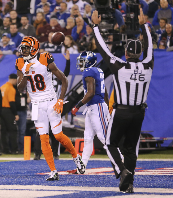 Cincinnati Bengals wide receiver A.J. Green (18) flips the ball aside after scoring a touchdown against the New York Giants during the first quarter of an NFL football game, Monday, Nov. 14, 2016, ...