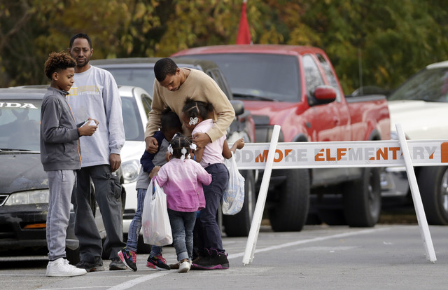 Children get a goodbye hug as students are picked up from Woodmore Elementary School on Tuesday in Chattanooga, Tenn. The school bus driven by Johnthony Walker, 24, crashed while transporting chil ...