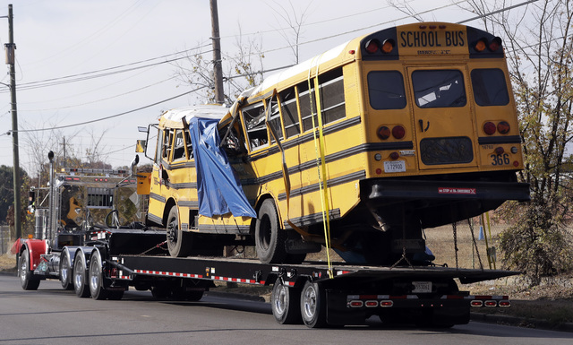 A school bus is carried away Tuesday, Nov. 22, 2016, in Chattanooga, Tenn., from the site where it crashed on Monday. The bus driver, Johnthony Walker, 24, has been arrested on charges including v ...
