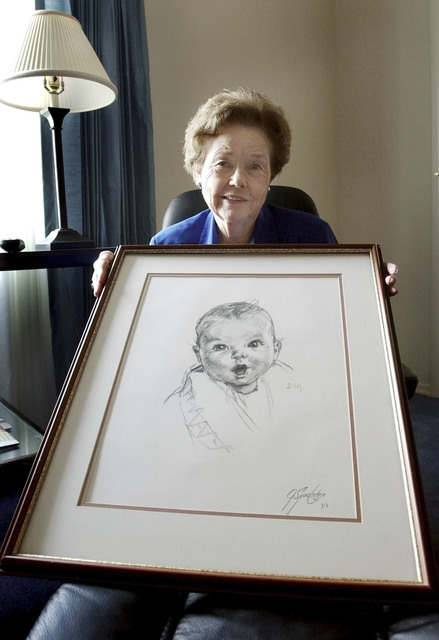 Ann Taylor Cook, poses at her Tampa, Florida, home in a 2004, with a copy of her photo that is used on all Gerber baby food products. Gerber says Cook turned 90 on Sunday, Nov. 20,. (Chris O'Meara/AP)