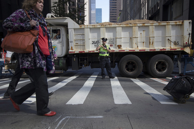 FILE- In this Sept. 24, 2015 file photo, a police office stands guard at a loaded dump truck that serves as a barricade along the perimeter of St. Patrick's Cathedral before the arrival of Pope Fr ...