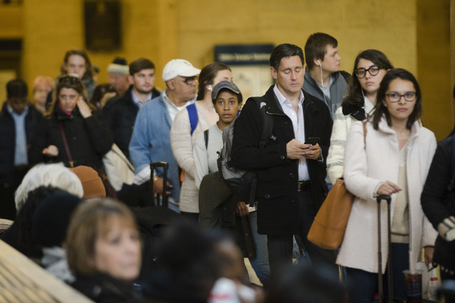 Travelers stand in line to board a train at the 30th Street Station ahead of the Thanksgiving Day holiday, in Philadelphia, Tuesday, Nov. 22, 2016. Almost 49 million people are expected to travel  ...