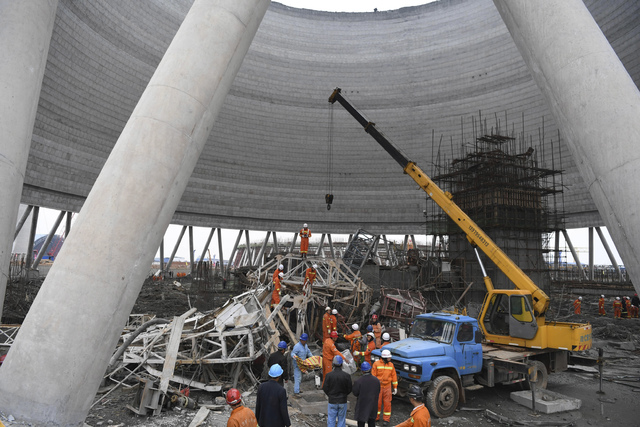 In this photo released by Xinhua News Agency, rescue workers look for survivors after a work platform collapsed at the Fengcheng power plant in eastern China's Jiangxi Province, Thursday, Nov. 24, ...
