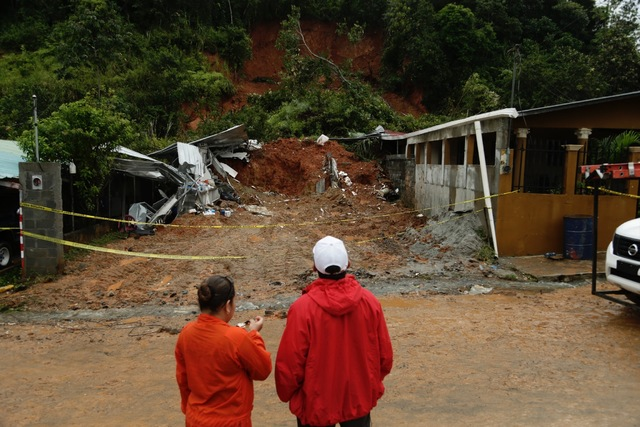 Civil Defense workers look the area where a couple was killed after their home was destroyed Tuesday by a mudslide in Arraijan on the outskirts of Panama City. (Arnulfo Franco/AP)