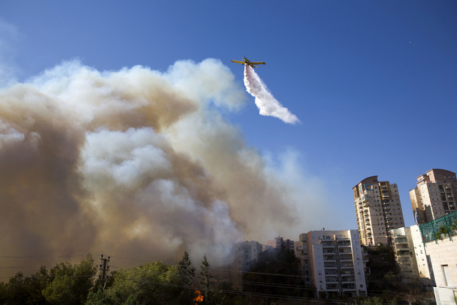 A plane flies over the wildfires in Haifa, Israel, Thursday, Nov. 24, 2016. Israeli police have arrested four Palestinians in connection with one of several large fires that damaged homes and prom ...