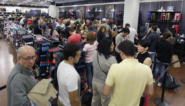 Shoppers stand in line to pay for their purchased merchandise at a Tommy Hilfiger store on Black Friday, Nov. 25, 2016, in Miami. Stores opened their doors Friday for what is still one of the busi ...