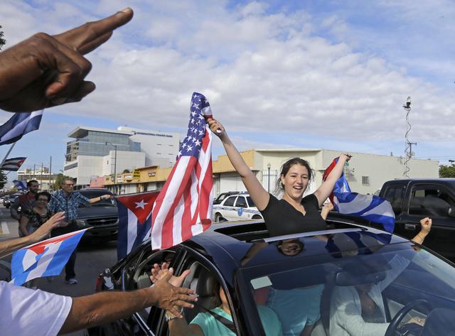 Cuban-Americans react to the death of Fidel Castro Saturday in the Little Havana area in Miami. (Alan Diaz/AP)