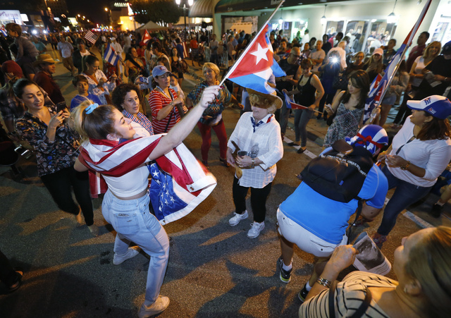 Members of the Cuban community dance in the street as they react to the death of Fidel Castro in front of the Versailles Restaurant in the Little Havana neighborhood of Miami. (Wilfredo Lee/AP)