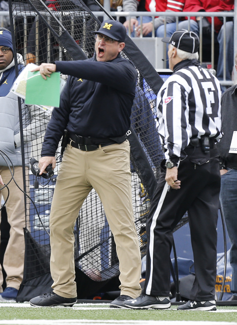 Michigan head coach Jim Harbaugh, left, yells at the field judge during the first half of an NCAA college football game  against Ohio State, Saturday, Nov. 26, 2016, in Columbus, Ohio. Ohio State  ...