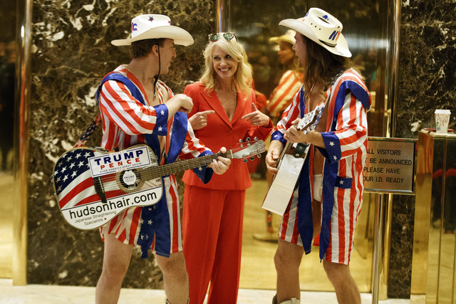 "Kellyanne Conway, campaign manager for President-elect Donald Trump, center, listens to a song by ""The Naked Cowboy,"" in the lobby of Trump Tower, Monday, Nov. 28, 2016, in New York. (Evan Vucci/AP)"