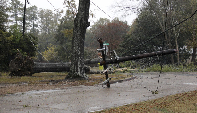 A utility pole lies across a street in north Greenwood, Miss., after it was knocked down by during a thunderstorm Monday, Nov. 28, 2016. The city also suffered power outages, additional downed tre ...