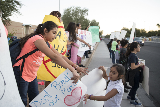 Maetzi Maximiliano, 11, left, student at Monaco Middle School, trades signs with her sister Jaqueline, 8, who goes to a different school, during a rally against (Erik Verduzco/Las Vegas Review-Jou ...