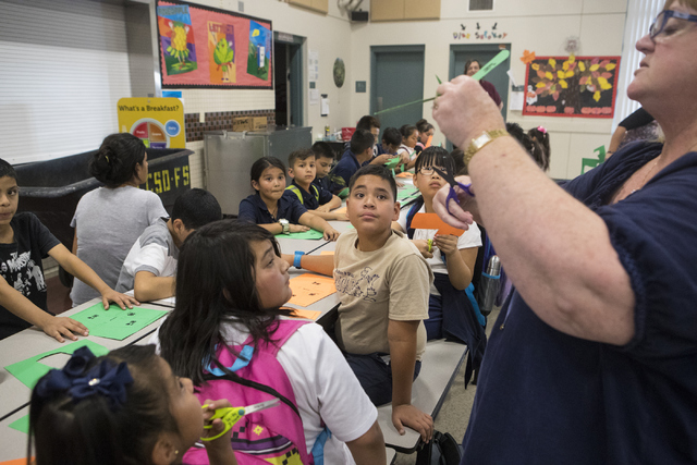 First-grade teacher Kim Raham instructs the children on how to build a FPG-9 foam plate glider during the ninth annual 4-H National Youth Science Day challenge at Diaz Elementary School Oct. 12, 2 ...