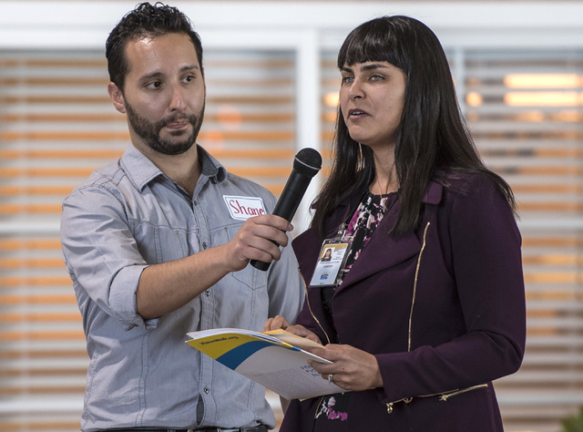 Shane Cullen holds a microphone for Raquel O'Neill as she uses brail to read a speech during a Las Vegas Chapter of the Foundation Fighting Blindness meeting at the RTC Mobility Training Center on ...