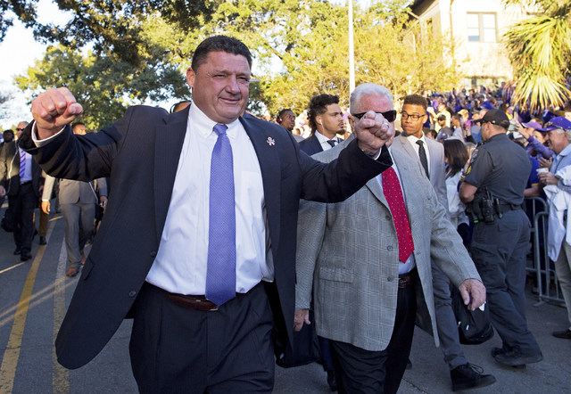 LSU coach Ed Orgeron waves to fans as he walks down Victory Hill as he arrives at Tiger Stadium with his team for an NCAA college football game agains Mississippi in Baton Rouge, La., Saturday, Oc ...