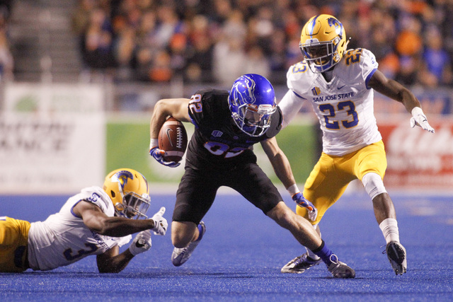Boise State wide receiver Thomas Sperbeck (82) carries the ball between San Jose State safety Trevon Bierria (23) and cornerback Jermaine Kelly (3) during the first half of an NCAA college footbal ...