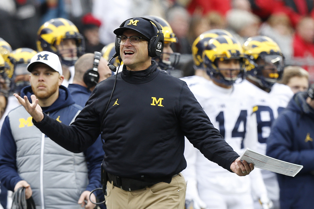Michigan head coach Jim Harbaugh walks the sidelines during the second half of an NCAA college football game Saturday, Nov. 26, 2016, in Columbus, Ohio. Ohio State beat Michigan 30-27 in double ov ...