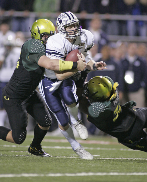 BYU quarterback John Beck, center, is tackled by Oregon's Nick Reed, left, and Blair Phillips, during the Las Vegas Bowl football game in Las Vegas, Thursday, Dec. 21, 2006. (AP Photo/R. Marsh Starks)