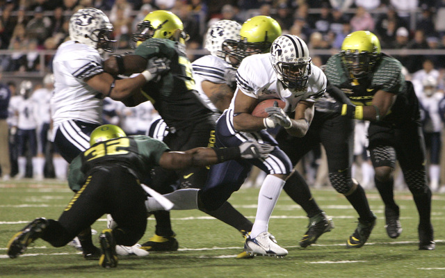Brigham Young's Curtis Brown, center, runs for a second-quarter touchdown as Oregon's Jairus Byrd (32) tries to tackle him during the Las Vegas Bowl football game in Las Vegas on Thursday, Dec. 21 ...
