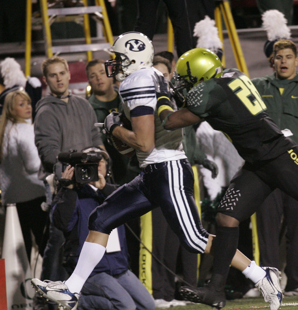 Brigham Young tight end Jonny Harline (13) runs a pass reception in for a touchdown in the second quarter against Oregon's  J.D. Nelson during the Las Vegas Bowl football game in Las Vegas on Thur ...