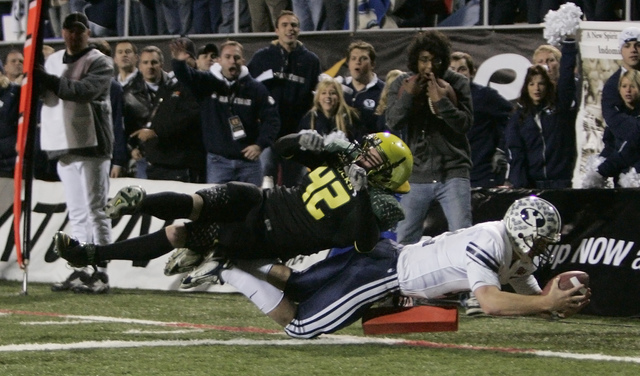 Brigham Young quarterback John Beck (12) dives for a touchdown against Oregon's Brent Haberly (42) in the forth quarter during the Las Vegas Bowl football game in Las Vegas on Thursday, Dec. 21, 2 ...