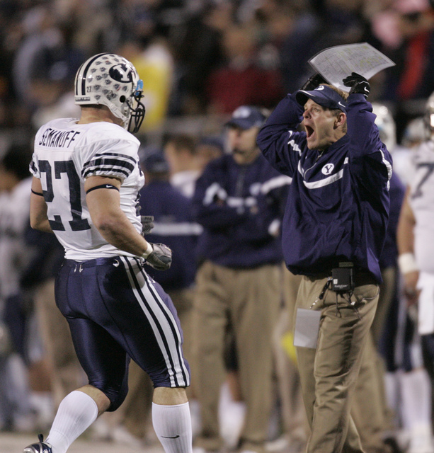 Brigham Young coach Mike Bellotti, right, yells to his players as Brigham Young's Joe Semanoff (27) runs off the field in the fourth quarter during the Las Vegas Bowl football game in Las Vegas on ...