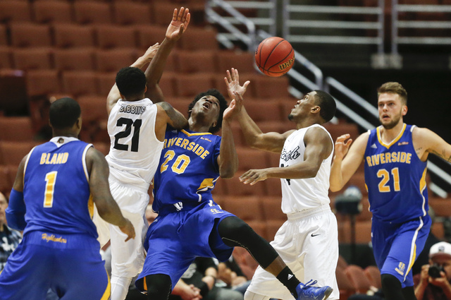 UC Riverside forward Secean Johnson, center, and Long Beach State guards Justin Bibbins, center left, and Branford Jones vie battle for a loose ball during the second half of an NCAA college baske ...
