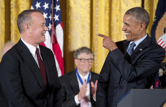 President Barack Obama, right, points at Tom Hanks, left, before presenting him with the Presidential Medal of Freedom during a ceremony in the East Room of the White House, Tuesday, Nov. 22, 2016 ...