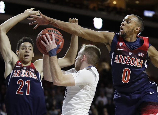Arizona's Parker Jackson-Cartwright, right, and Chance Comanche, left, try to block Butler's Tyler Lewis during the second half of an NCAA college basketball game Friday, Nov. 25, 2016, in Las Veg ...