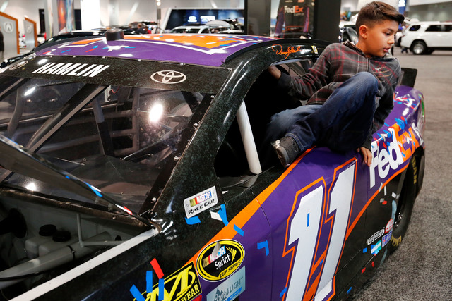 Kristofer Mata, 10, of Las Vegas gets out from  the NASCAR race car No.11 FedEx Toyota Camry after sitting the driver's seat during the Motor Trend International Auto Show at the Las Vegas Convent ...