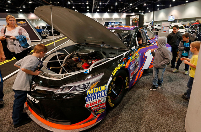 Children check out the NASCAR race car No.11 FedEx Toyota Camry during the Motor Trend International Auto Show at the Las Vegas Convention Center in Las Vegas, Sunday, Nov. 27, 2016. Chitose Suzuk ...