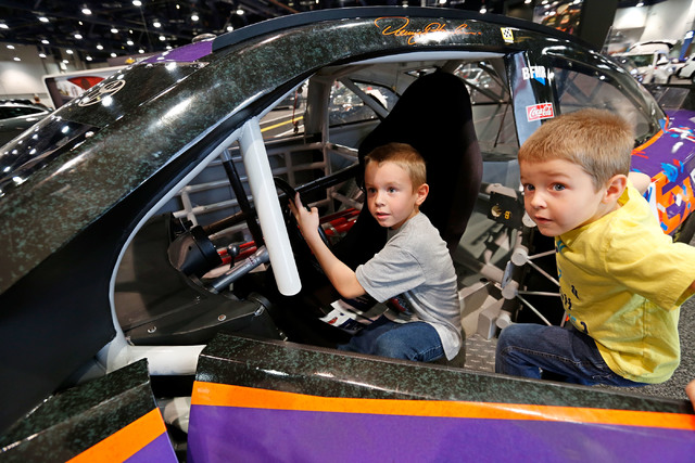 Grayson Gregory, 6, of Las Vegas, left, and his brother Nolan, 4, check out  the NASCAR race car No.11 FedEx Toyota Camry during the Motor Trend International Auto Show at the Las Vegas Convention ...