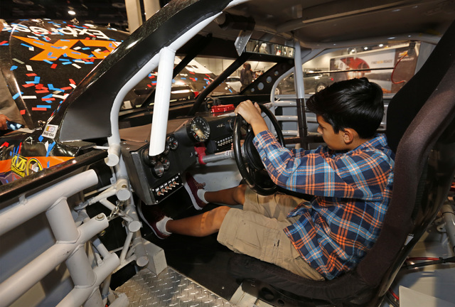 Gabriel Lugo, 10, of Las Vegas sits on the driver's seat of the NASCAR race car No.11 FedEx Toyota Camry during the Motor Trend International Auto Show at the Las Vegas Convention Center in Las Ve ...