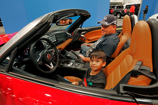 Jayden West, 7, of North Las Vegas, foreground and his father Johnny sit on a Fiat Spider Lusso 2017 model during the Motor Trend International Auto Show at the Las Vegas Convention Center in Las  ...