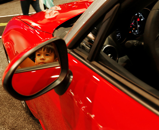 Jayden West, 7, of North Las Vegas is reflected in a side mirror of Fiat Spider Lusso 2017 model as sitting on the car with his father Johnny during the Motor Trend International Auto Show at the  ...