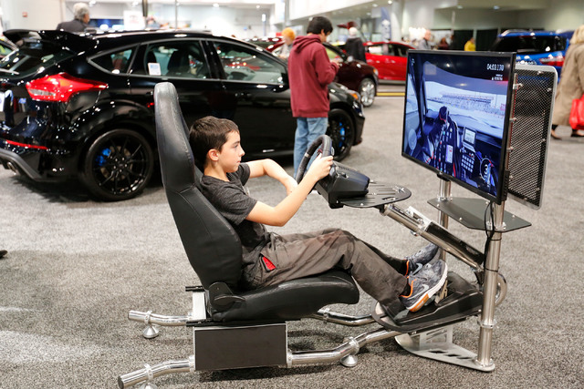 Aiden Passage, 12, of Las Vegas tries to steer a car in a simulation during the Motor Trend International Auto Show at the Las Vegas Convention Center in Las Vegas, Sunday, Nov. 27, 2016. Chitose  ...