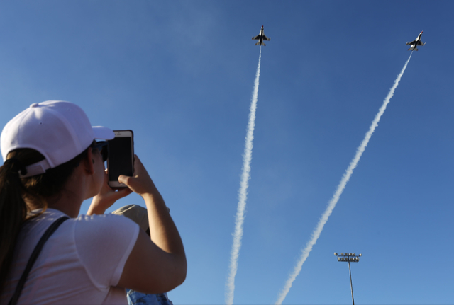 A woman takes a photo of the Thunderbirds passing over the audience during the 2016 Aviation Nation air show on Nellis Air Force Base in Las Vegas on Friday, Nov. 11, 2016. Brett Le Blanc/Las Vega ...
