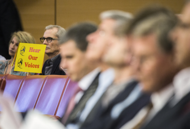 A couple holds a sign while members of EHB Companies, right, listens during a Las Vegas City Council public hearing on the controversial large-scale development on the Badlands Golf Course on Wedn ...