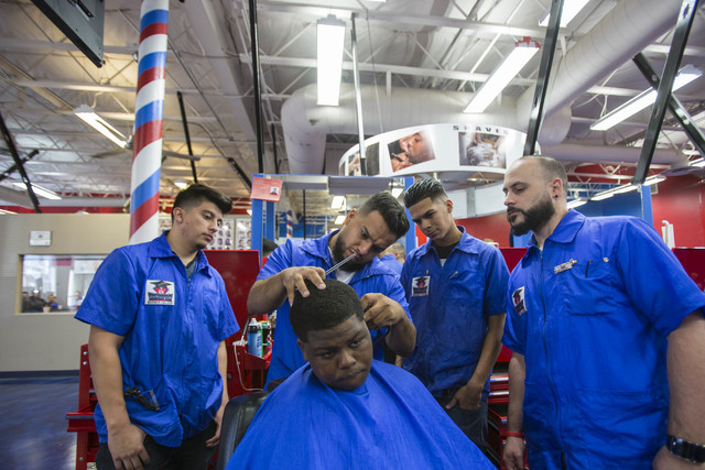 Barber student Christian Diaz, second left, freestyles a design in the hair of customer Tristan Clay, 14, as fellow students look on during class at the Masterpiece Barber College in Las Vegas, Th ...