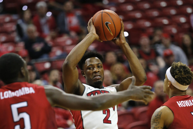 UNLV Rebels guard Uche Ofoegbu (2) keeps a ball away from Western Kentucky Hilltoppers guard Junior Lomomba (5) and Western Kentucky Hilltoppers guard Tobias Howard (1) during the first half of a  ...