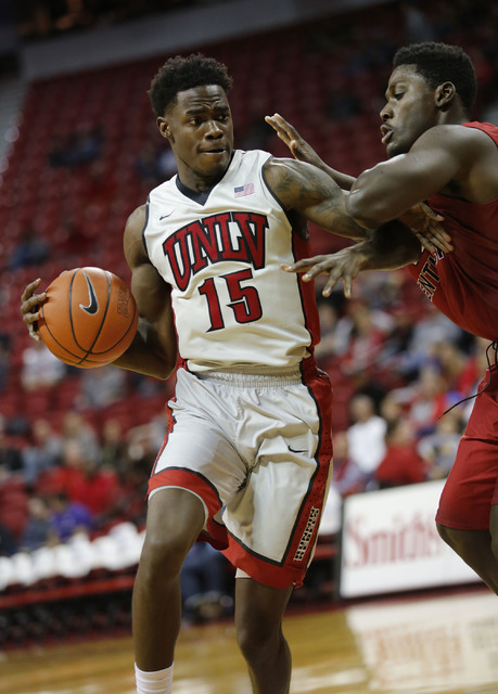UNLV Rebels forward Dwayne Morgan (15) keeps a ball away from Western Kentucky Hilltoppers forward Anton Waters (42) during the second half of a basketball game at the Thomas & Mack Center in  ...