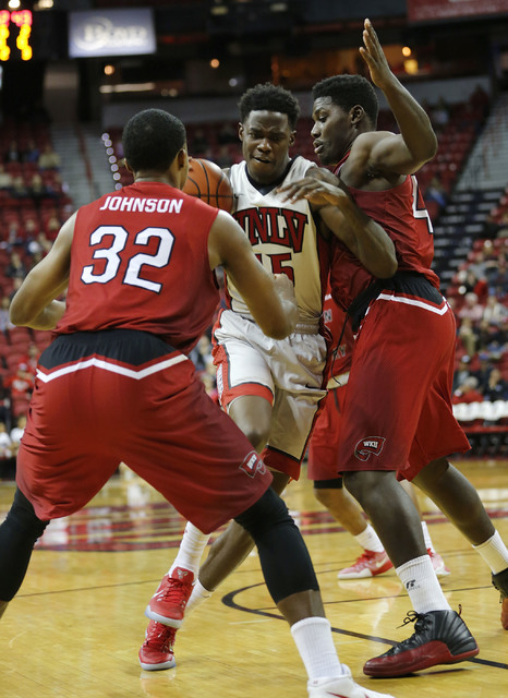 UNLV Rebels forward Dwayne Morgan (15) tries to drive past Western Kentucky Hilltoppers guard Que Johnson (32) and Western Kentucky Hilltoppers forward Anton Waters (42) during the second half of  ...