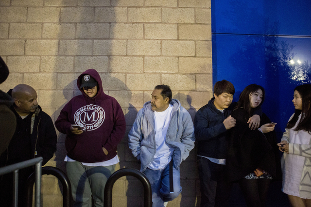 Nico Garcia, center, and Nico Garcia Jr.,center left,  Black Friday shoppers that had camped outside of the Best Buy in Summerlin since Saturday, Nov. 19, 2016, stand against the wall waiting to e ...