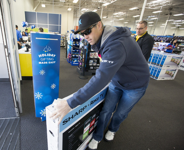 5d80a11460b A Black Friday costumer pushes a Sharp 55-inch TV out the door after  purchasing