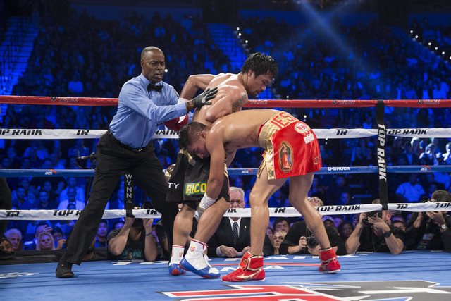 Manny Pacquiao, left, watches his opponent Jessie Vargas lose his balance in their welterweight WBO World Title bout at the Thomas & Mack Center on Saturday, Nov. 5, 2016, in Las Vegas. Pacqui ...