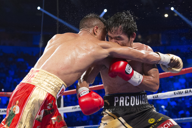 Jessie Vargas, left, battles Manny Pacquiao at the end of a round in their welterweight WBO World Title bout at the Thomas & Mack Center on Saturday, Nov. 5, 2016, in Las Vegas. Pacquiao won b ...