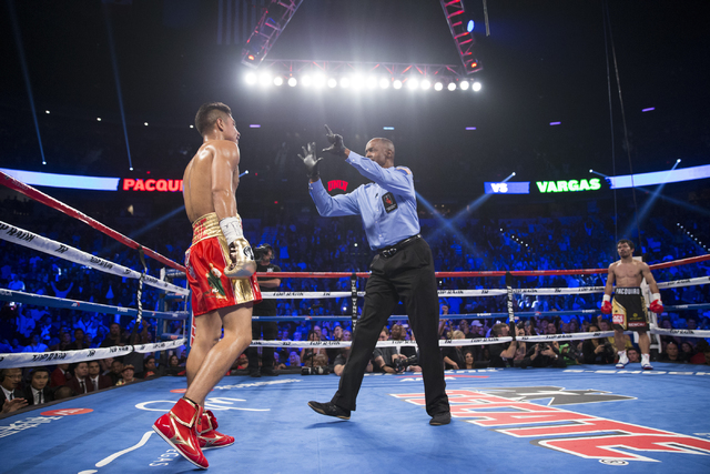 Jessie Vargas, left, gets a count after getting knocked down by his opponent Manny Pacquiao in their welterweight WBO World Title bout at the Thomas & Mack Center on Saturday, Nov. 5, 2016, in ...