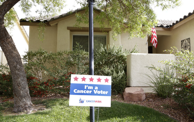 """I'm a Cancer Voter"" yard sign is seen in the front yard of Sherry Jasperson's home Friday, Oct. 28, 2016, in Las Vegas. Sherry is the state lead for the American Cancer Society, ..."